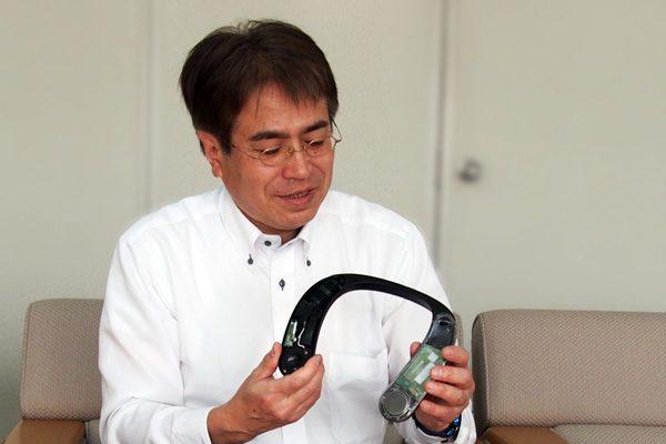 ネックスピーカー試作機を持つ開発担当の蓑田さん