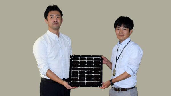 化合物事業推進部 主任の植田 浩介(左)と同 田中 康裕 手に持つのは、世界最高水準の「Ⅲ-Ⅴ化合物3接合型太陽電池モジュール」