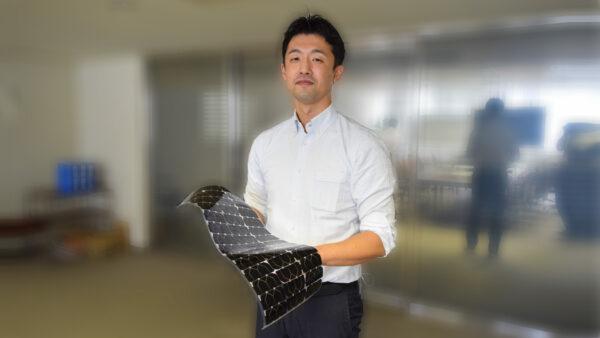 化合物事業推進部 主任の植田 浩介 手に持つのは、ドローンなどの無人航空機向けの太陽電池モジュール